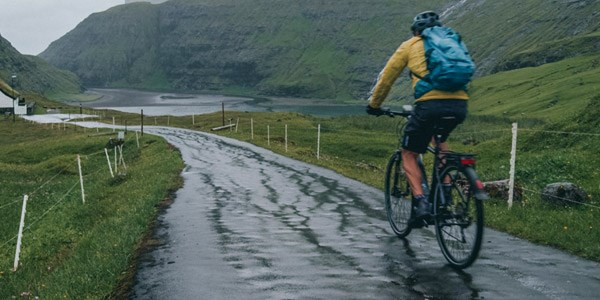 A cycling uses a rear mudguard to stop road spray flinging upwards and over his back