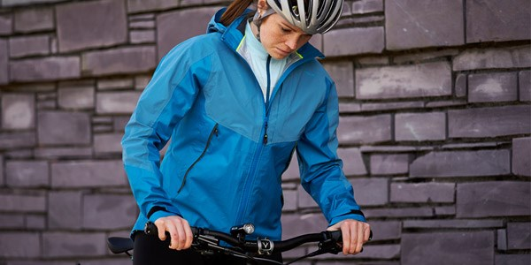 A cycle commuter wearing multiple layers with a waterproof jacket on top