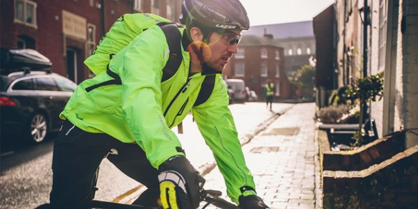 A road cyclist wearing a lightweight packable waterproof jacket