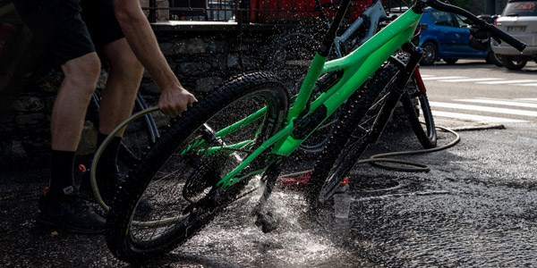 A mountain biker cleaning their wheels & tyres