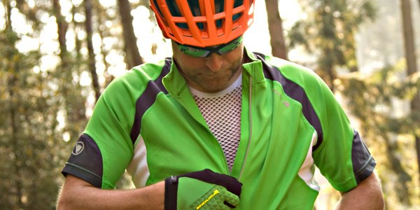 A mountain biker layering a base layer with a jersey