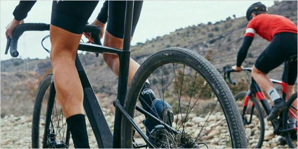 Two cyclists riding over rough terrain on the Topstone Carbon 2020