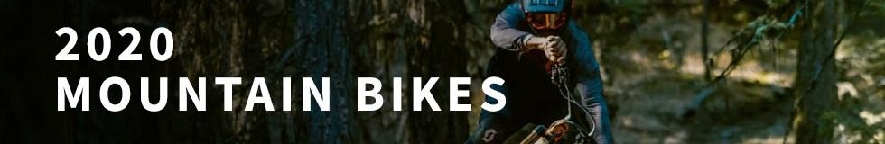 A mountain biker hitting a jump on a 2020 Scott MTB