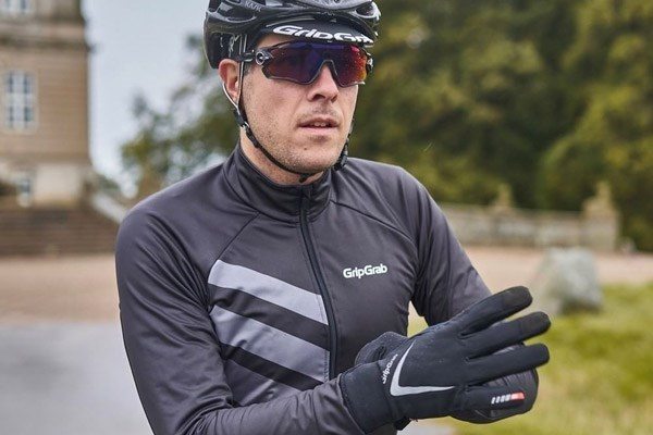 A cyclist putting on a pair of cycling gloves