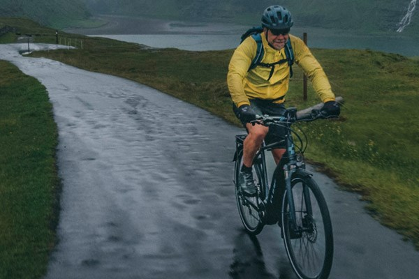 A cycling in bad weather wearing a waterproof jacket