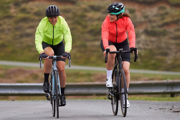 Two cyclists wearing lightweight, waterproof jackets