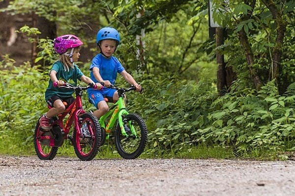 Two kids ride on a gravel trail