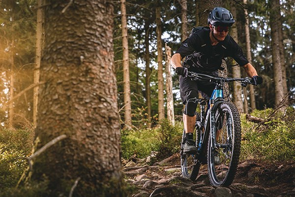A mountain biker riding over a rocky & rooty trail