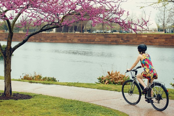 female biker cycling by the river